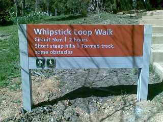 Sign that reads: Whipstick Loop Walk. 5km circuit, take two hours. Short steep hills. Formed track with some obstacles.