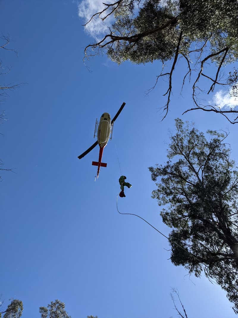 Project firefighter dripping out of helicopter in sky